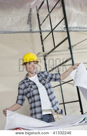 Happy young worker holding building plans while looking away