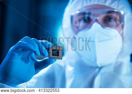 Microelectronics engineer works in a modern scientific laboratory on computing systems and microprocessors. Electronic factory worker is testing the motherboard and coding the firmware.