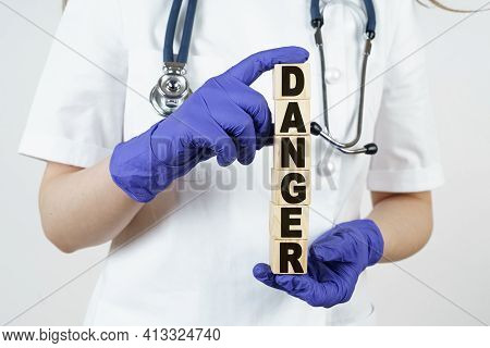 Medicine And Health Concept. The Doctor Holds Cubes In His Hands On Which It Is Written - Danger