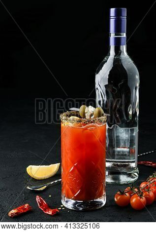 Fresh Alcoholic Cocktail Bloody Mary With Vodka, Tomatoes, Olive And Spice In Glass Next To Bottle O