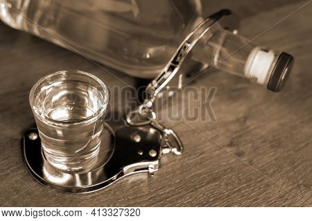 Close-up And Selective Focus Of Shot Glass Of Vodka Strapped With Metal Police Handcuffs To Bottle.