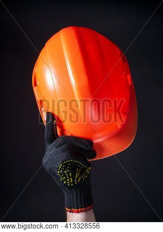 Orange Construction Helmet Close-up. The Man Makes A Greeting Gesture With An Orange Construction He
