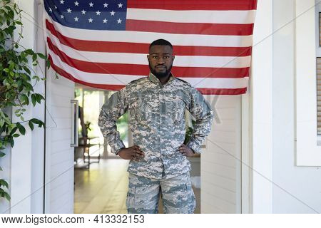 African american male soldier standing in front of american flag outside home. . soldier returning home to family.