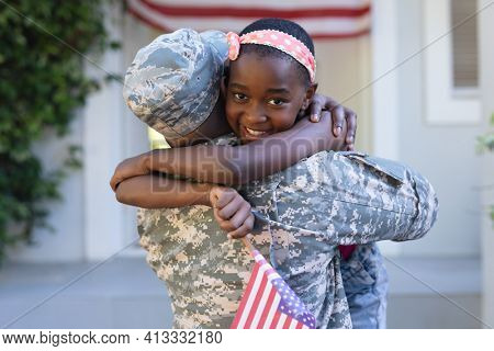 African american soldier father hugging smiling daughter holding flag in front of house. soldier returning home.