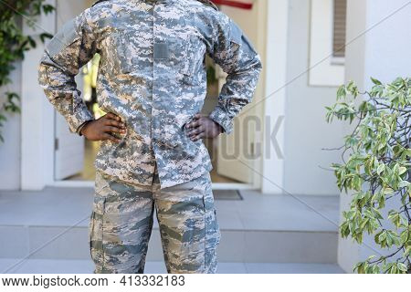 Midsection of african american male soldier standing outside his home. soldier returning home to family.