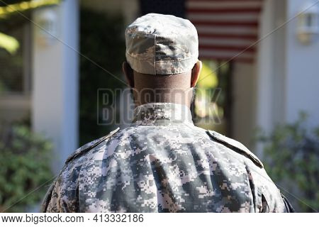 Rear view of african american male soldier standing in front of american flag outside home. soldier returning home to family.