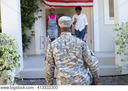 Rear view of african american soldier father greeting son and daughter in front of house. soldier returning home to family.