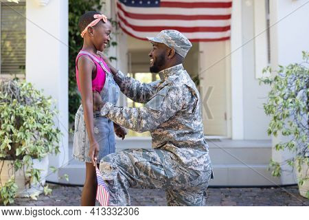 African american male soldier father greeting smiling daughter holding flag in front of house. soldier returning home.