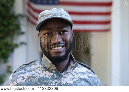 Portrait of smiling african american male soldier standing in front of american flag outside home. soldier returning home to family.