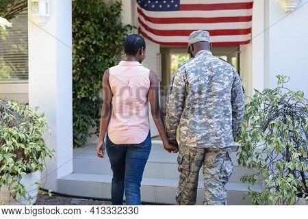 Rear view of african american male soldier and wife standing holding hands in front of their house. soldier returning home to family.