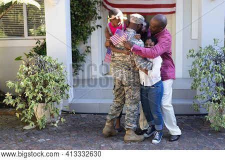 African american soldier father hugging wife, children and father in front of their house. soldier returning home to family.