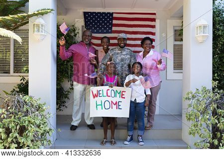 African american soldier father with smiling wife, children and parents in front of their home. soldier returning home to family.