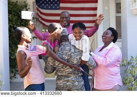African american soldier father greeting his smiling three generation family in front of the house. soldier returning home to family.