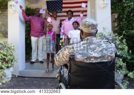 African american soldier father in wheelchair greeting smiling three generation family outside home. soldier returning home to family.