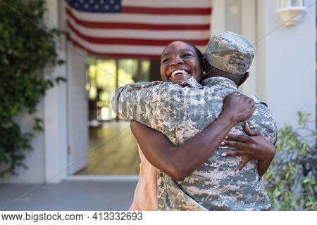 African american male soldier hugging smiling wife in front of american flag outside house. soldier returning home to family.