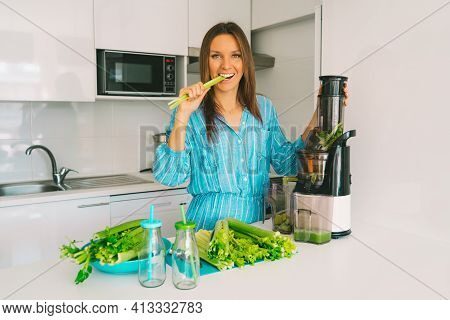 Healthy Young Woman Making Freshly Pressed Celery Juice In Juicer Machine At Home In Kitchen. Fresh