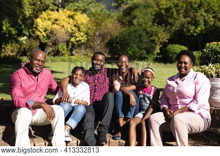 Smiling african american parents with children and their grandparents sitting embracing outdoors. three generation family spending time together.