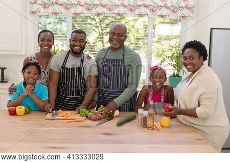 Portrait of happy african american parents with son and daughter and grandparents in the kitchen. three generation family spending quality time together.
