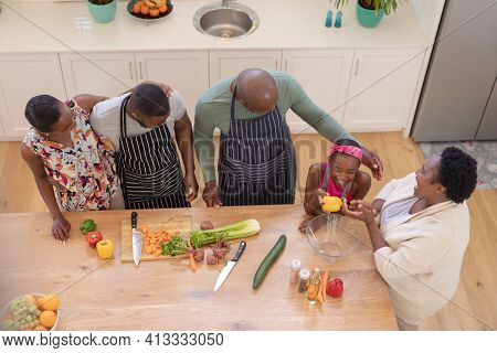African american parents cooking with son and daughter and grandparents in the kitchen. three generation family spending quality time together.