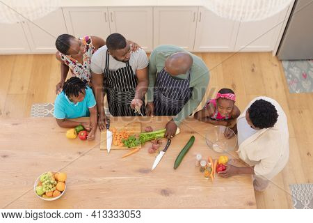 African american parents cooking with son and daughter and grandparents in the kitchen. three generation family spending quality time together. . three generation family spending quality time