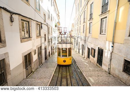 Trams In Lisbon City. Famous Retro Yellow Funicular Tram On Narrow Streets Of Lisbon Old Town On A S