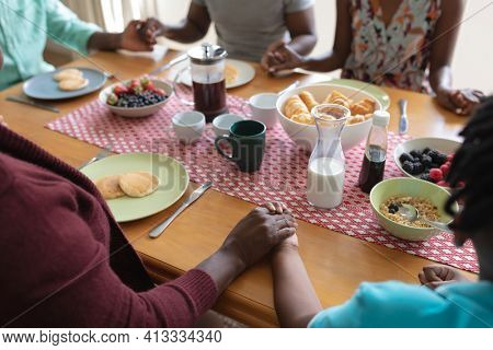 Midsection of african american parents, son and grandparents holding hands in prayer at dinner table. three generation family spending quality time together.
