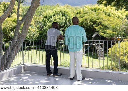 Senior african american father and adult son standing on terrace in sunny garden. happy family spending time together at home.
