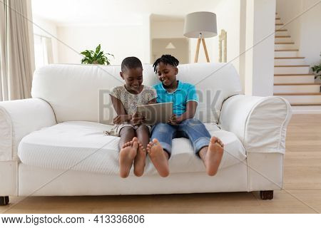 Smiling african american brother and sister sitting on couch using digital tablet. staying at home in isolation during quarantine lockdown.