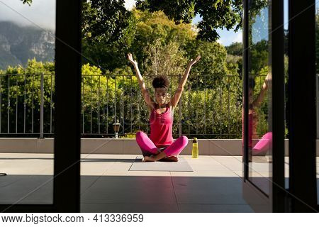 Mixed race woman exercising practicing yoga on a terrace. staying at home in isolation during quarantine lockdown.