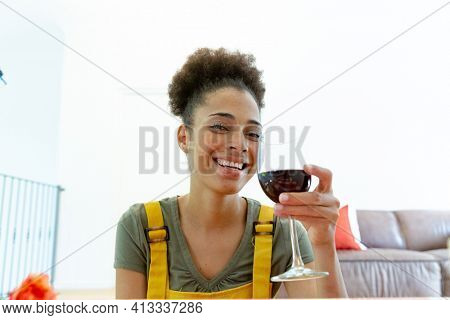Mixed race woman drinking a glass of wine and smiling at home. staying at home in isolation during quarantine lockdown.
