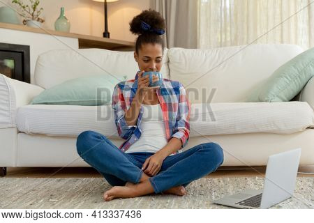 Mixed race woman sitting on the floor using laptop and drinking coffee at home. staying at home in isolation during quarantine lockdown.
