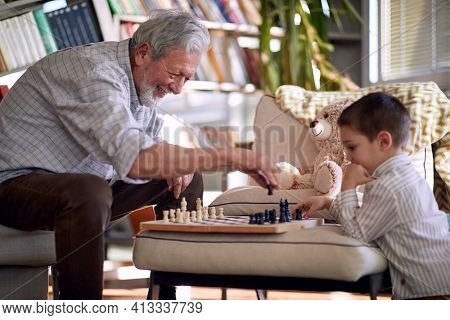 A happy grandpa in a relaxed atmosphere at home enjoy teaching his little grandson how to play a chess. Family, home, playtime
