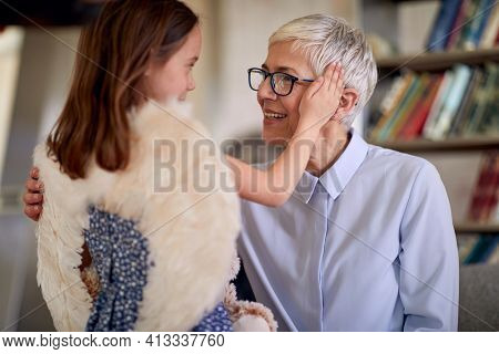 A grandma and her little granddaughter are cuddling each other while spending a time together in family atmosphere at home. Family, home, love, playtime