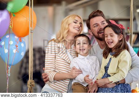 Young parents and their kids enjoy posing for a photo while sitting on the swing together in a cheerful atmosphere at home. Family, home, playtime