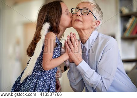 A little girl with angel wings is kissing and exchanging emotions with her grandmother in a family atmosphere at home. Family, home, love, playtime