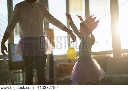 A little daughter and her father dancing while they having a ballet training in a relaxed atmosphere at home. Family, ballet, training