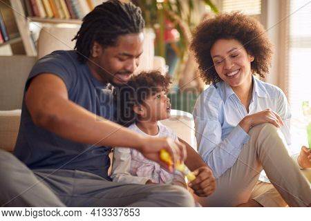 Young parents and their little daughter sitting on the floor in a relaxed atmosphere at home and preparing a liquid to make soap bubbles. Family, home, playtime