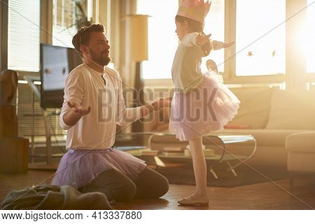A young father correcting his little ballerina posture while they have a ballet training in a relaxed atmosphere at home. Family, ballet, training