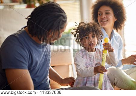 A cute little girl posing for a photo while playing with her parents in a playful atmosphere at home. Family, together, playtime