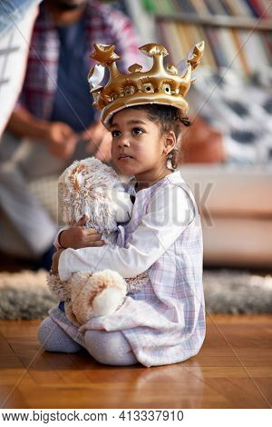A cute little girl with a crown on her head holding a teddy while playing on the floor in a relaxed atmosphere at home. Family, home, playtime