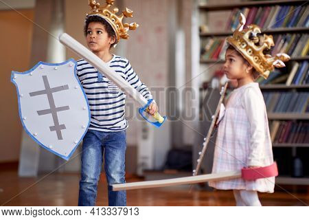 A little brother and sister dressed like knights are playing in a cheerful atmosphere at home. Family, home, playtime