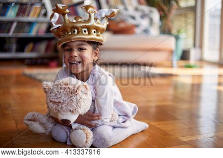 A cute little girl with a crown on her head sitting on the floor in a relaxed atmosphere at home and posing for a photo while hugging a teddy bear. Family, home, playtime