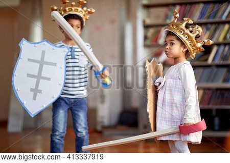 A little brother and sister dressed like knights are having a good time while playing in a cheerful atmosphere at home. Family, home, playtime