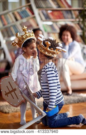 Children dressed as knights whisper and murmur while spending a quality time with their parents in a relaxed atmosphere at home. Family, home, playtime