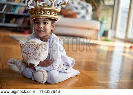 A cute little girl with a crown on her head holding a teddy and posing for a photo while playing in a relaxed atmosphere at home. Family, home, playtime