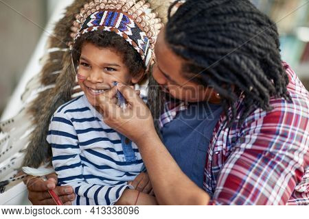 A little boy dressed like an Indian enjoying while father is drawing on his face in a playful atmosphere at home. Family, home, playtime