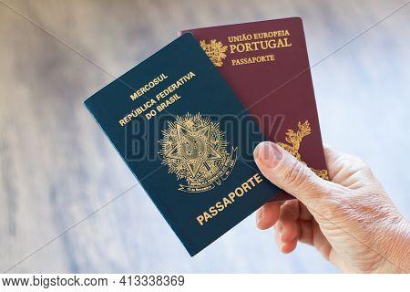 Hand Holding Portuguese Passport And Brazilian Passport.