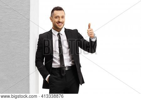 Man in a black suit and tie leaning on wall and showing thumbs up isolated on white background