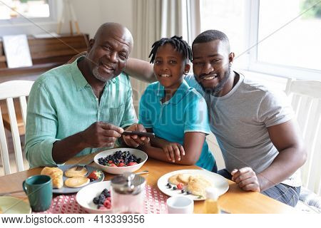 Happy african american father, grandfather and boy sitting at table and eating. three generation family spending quality time together.