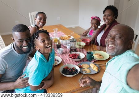 Happy african american grandfather taking selfie with grandchildren and their parents at family meal. three generation family spending quality time together.